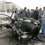 Iraqi policemen examine the remains of a vehicle used in a bomb attack in Najaf